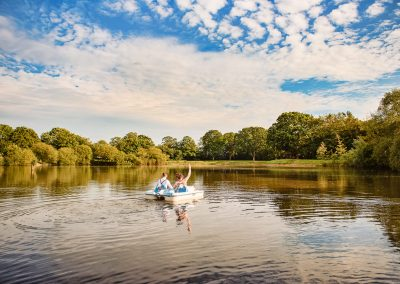 Wedding photo of bride and groom in a pedalo at Sopley Lake wedding venue