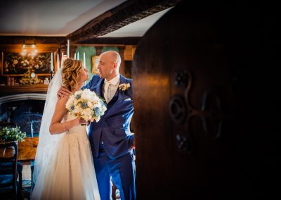 Bride and groom private moment bwhind wooden door is photographed at Athelhampton House wedding venue in Dorset