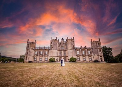Bride and groom walk hand in hand at sunset outside Dorset castle wedding venue
