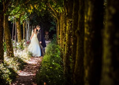 Bride and groom wedding couple photo taken through green tree tunnel at Athelhampton House wedding venue