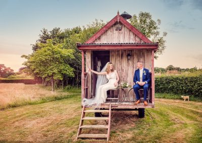 Bride and groom sit in shabby chic wooden trailer house in countryside photo by one thousand words documentary wedding photographers