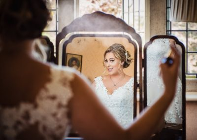 Documentary weddign photo of bride spraying hair in mirror on wedding morning at Studland Bay House wedding venue in Dorset