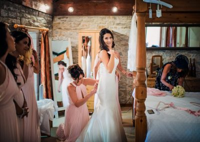 Bride is laced into weddign dress by bridesmaids in pink on wedding morning at Kingston Country Courtyard photo by one thousand words