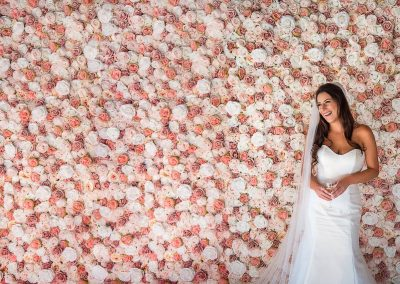 Laughing bride in white wedding dress stands next to huge pink and white rose flower wall
