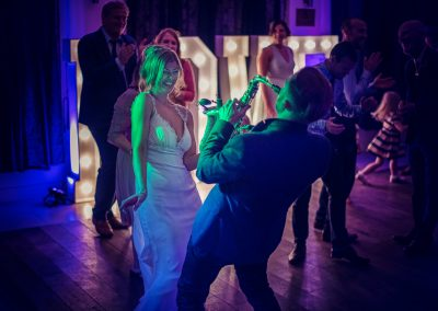 Wedding photograph of bride dancing with saxophonist on dancefloor at The Italian Villa wedding venue in Dorset
