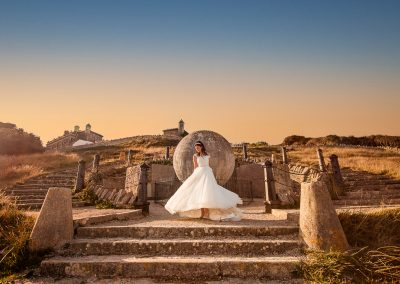 Bride in white wedding dress twirls in front of Victorian stone globe at Durlston Castle wedding venue in Dorset