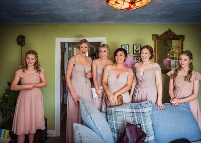 Bridesmaids in pink pastel dresses shock reactions to bride in wedding dress captured by one thousand words documentary wedding photographs