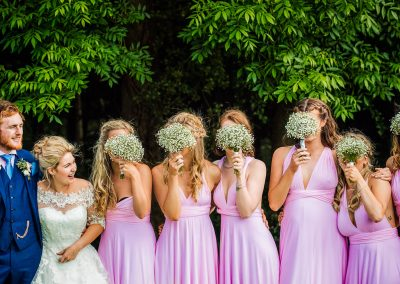 Bridesmaids in pink dresses hide their faces during group wedding photographs by one thousand words photography