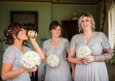 Bridesmaids in silver sequinned dresses drink cider at Parley Manor wedding venue photos by one thousand words