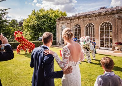 Chinese dragon dance watched by bride and groom at Sherborne castle wedding in Dorset