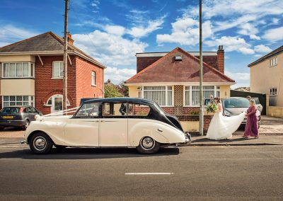 Classic wedding car outside family home with bride and bridesmaid