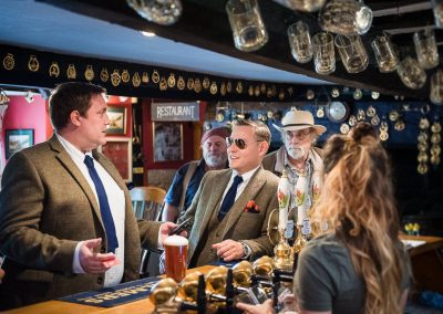 Groom and best man in tweed suits drink beer in traditional English pub on wedding morning in Dorset