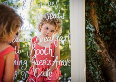 Cute child wedding guest portrait photograph taken in wedding plan mirror