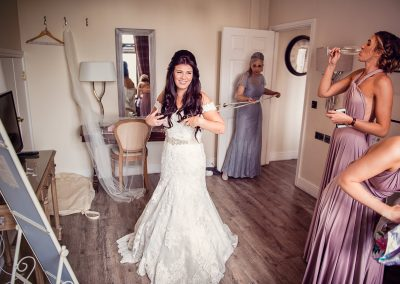 Froyle Park wedding venue morning bride is laced into wedding dress as bridesmaids drink champagne