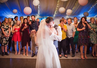 Bride and groom in an emotional embrace during first dance surrounded by guests in the marquee at Parley Manor