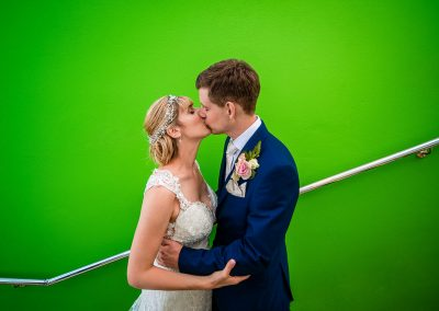 Wedding couple photo of bride and groom kissing in front of green wall
