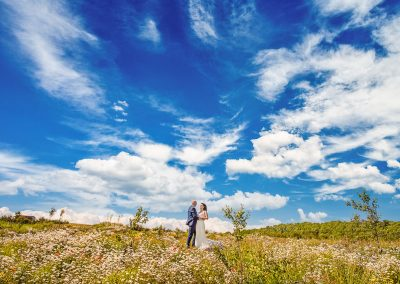 Dorset countryside wedding photograph of bride and groom in a flower field with bright blue cloudy sky