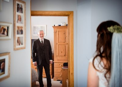 Wedding photo of the father of the bride reacting to seeing his daughter in her wedding dress for the first time