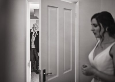 Black adn white documentary wedding photograph of father of bride waitign for nervour bride outside doorway on wedding morning