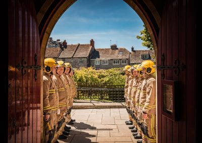 Wedding photo of firemen in uniform guard of honour outside church doorway