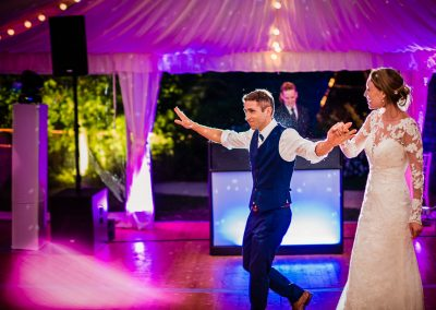 Backlit groom leads bride in white wedding dress onto multicoloured dancefloor in wedding marquee