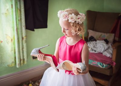 Flower girl wearing floral headpiece examines the red soles of diamante louboutin wedding shoes on weddign morning