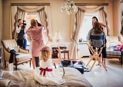 Flower girl takes photographs of bridal suite during wedding morning preparations