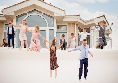 Fun wedding photograph of child wedding guests jumping from hotel onto beach