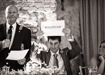 Black and white wedding photo of wedding guest holding up