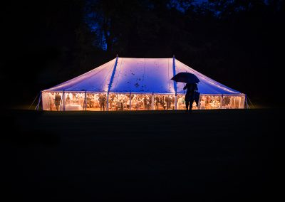 Documentary wedding photo of glowing wedding marquee and guest with umbrella silhouetted at Plush Manor in Dorset