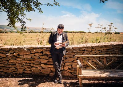 Groom in black tie leans on countryside wedding venue wall laughs as her reads letter from his bride on summer wedding morning