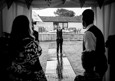 Black and white wedding photo of groom embracing rain outside wedding marquee watched by guests in the doorway