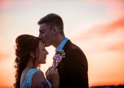 wedding couple photo of groom kissing happy bride on forehead at sunset