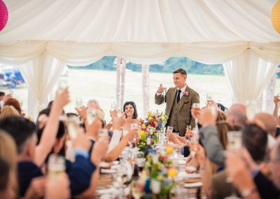 Groom in brown tweed suit raises glass at countryside marquee wedding breakfast
