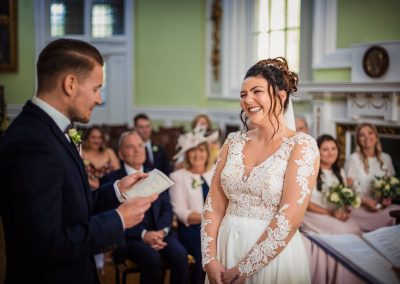 Bride in white wedding dress laughs as groom reads vows in Bournemouth Town Hall