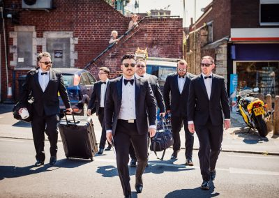 Documentary wedding photograph of groomsmen in black tie walking through Swanage town center