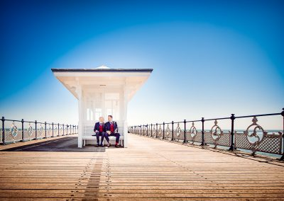 Stylish grooms sit in shelter on Swanage Victorian pier