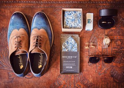 Photograph of grooms wedding shoes, sunglasses, ties, watch, cufflinks and camera film
