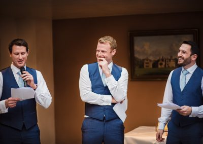 Groomsmen in blue wedding waistcoats laughing during wedding speeches