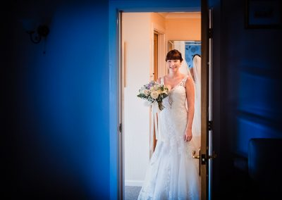 Happy bride with wedding bouquet and white dress stands in doorway