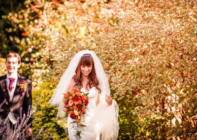 Happy bride with orange and red bouquet walks through Hethfelton House grounds
