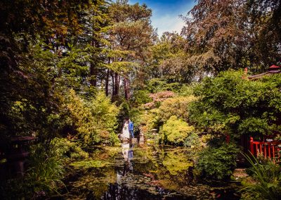 Bride and groom standing on stepping stones in Japanese gardens at Italian Villa wedding venue in Dorset