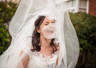 Documentary wedding photograph of bride laughing as white veil is blown over her face
