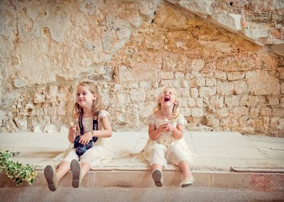Flower girls laughing at stone castle wedding venue