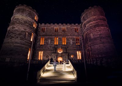 Lulworth Castle wedding venue lit at night under stars with bride and groom holding hands on the stone staircase