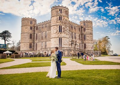 Wedding photo of Lulworth Castle in Dorset with bride and groom kissing on grounds on summer wedding day