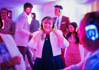 Wedding photography of mother of the bride enjoying the silent disco in a glowing marquee
