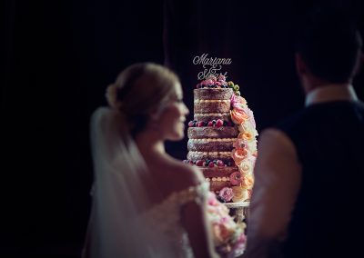 Photograph of bride and groom examining large naked wedding cake at Rhinefield House Hotel