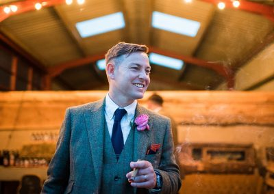 Natural groom portrait photograph smoking cigar in tweed suit outside countryside barn