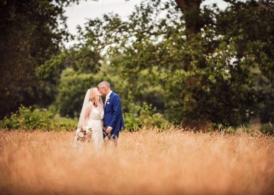 Countryside wedding photograph of bride and groom kissing in field of grass by one thousand words